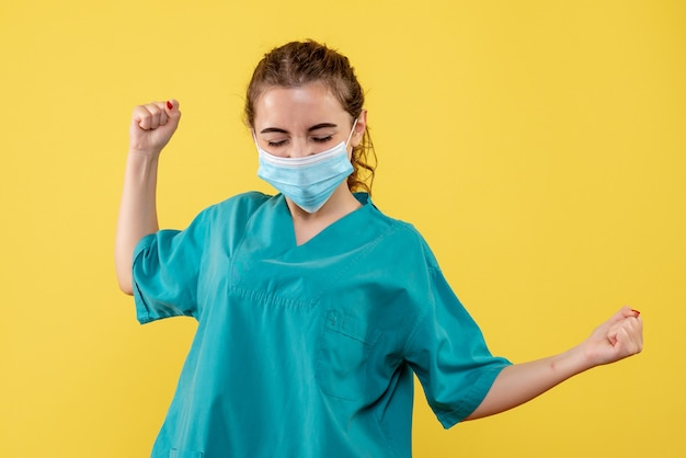 Vooraanzicht vrouwelijke arts in medisch overhemd en masker, gezondheid pandemie kleur covid-19 virus uniform