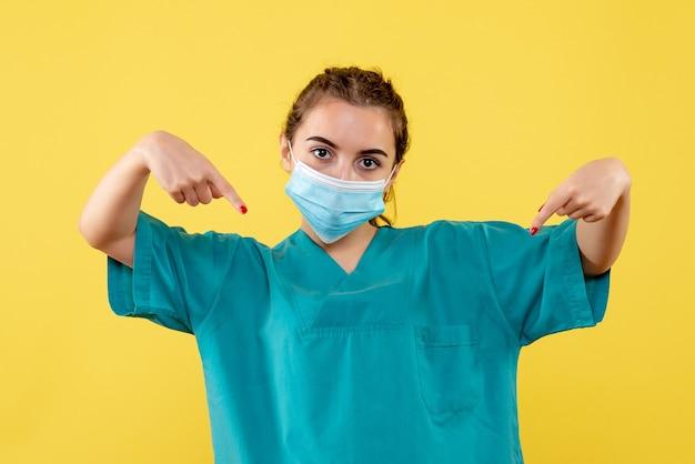 Vooraanzicht vrouwelijke arts in medisch overhemd en masker, gezondheid pandemisch virus covid-19 uniform coronavirus