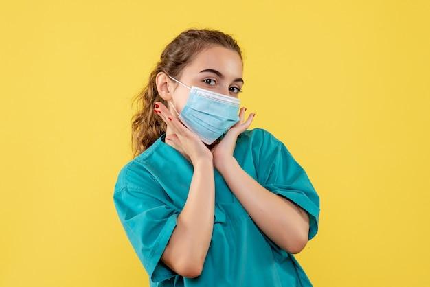 Vooraanzicht vrouwelijke arts in medisch overhemd en masker, gezondheid uniforme virus covid pandemische kleur
