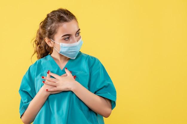 Vooraanzicht vrouwelijke arts in medisch overhemd en masker, kleur van het gezondheids de uniforme virus covid