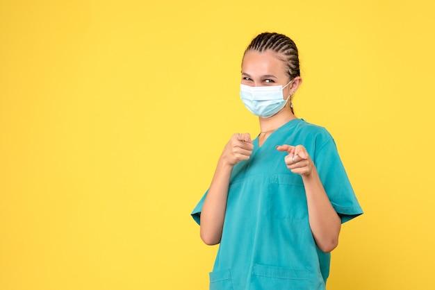 Vooraanzicht vrouwelijke arts in medisch overhemd en masker lachen, dokter gezondheid verpleegster virus pandemie covid-19 ziekenhuis