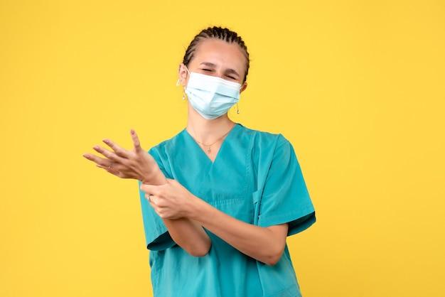 Vooraanzicht vrouwelijke arts in medisch overhemd en masker met gekwetste arm, gezondheidsverpleegkundige virus pandemie ziekenhuis covid-19 medic