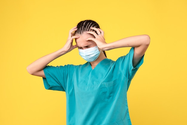 Vooraanzicht vrouwelijke arts in medisch overhemd en masker met hoofdpijn, gezondheidsverpleegster pandemie ziekenhuis covid-19 medic