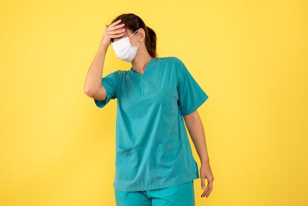 Vooraanzicht vrouwelijke arts in medisch overhemd en masker met hoofdpijn op gele achtergrond
