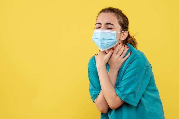 Vooraanzicht vrouwelijke arts in medisch overhemd en masker met keelpijn, pandemisch gezondheidsvirus covid-19 kleuruniform