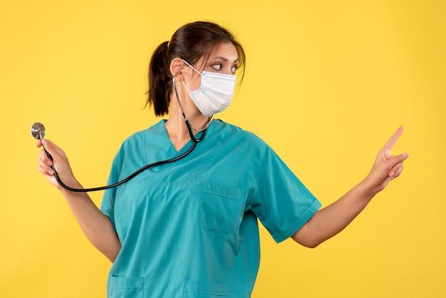 Vooraanzicht vrouwelijke arts in medisch overhemd en masker met stethoscoop op geel bureau gezondheid covid virus ziekenhuis medic pandemie