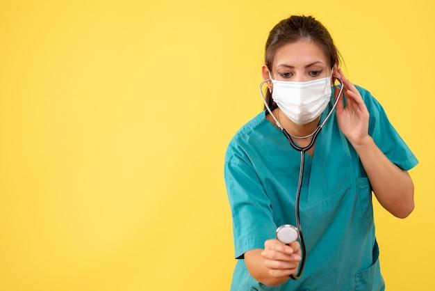 Vooraanzicht vrouwelijke arts in medisch overhemd en masker met stethoscoop op gele achtergrond