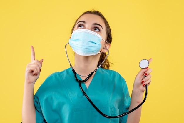 Vooraanzicht vrouwelijke arts in medisch overhemd en masker met stethoscoop, virus uniforme kleur emotie covid-19 gezondheid