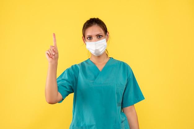 Vooraanzicht vrouwelijke arts in medisch overhemd en masker op gele achtergrond