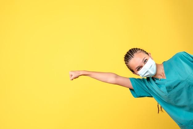 Vooraanzicht vrouwelijke arts in medisch overhemd en masker, pandemie gezondheid ziekenhuis covid kleur verpleegster