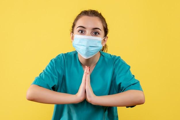 Vooraanzicht vrouwelijke arts in medisch overhemd en masker, pandemisch gezondheidsvirus covid-19 kleuruniform