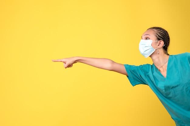 Vooraanzicht vrouwelijke arts in medisch overhemd en masker, pandemisch virus gezondheid covid kleur verpleegster ziekenhuis