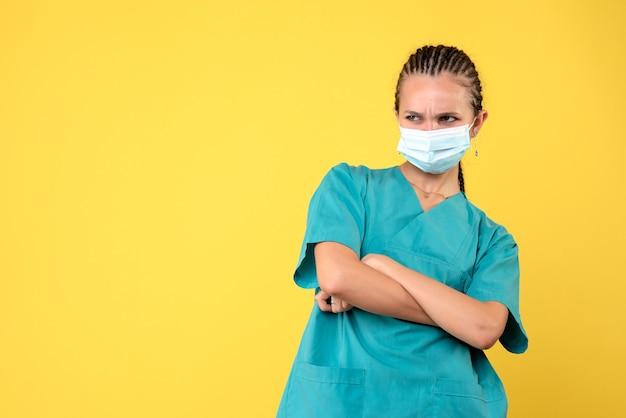 Vooraanzicht vrouwelijke arts in medisch overhemd en masker, pandemische kleur van het gezondheidsverpleegstervirus covid-19