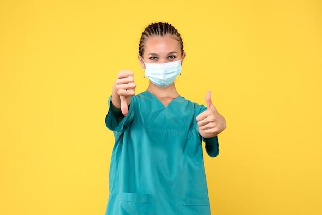 Vooraanzicht vrouwelijke arts in medisch overhemd en masker, pandemische medic gezondheid covid-19 ziekenhuisverpleegster virus