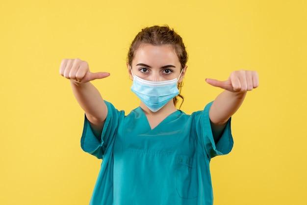 Vooraanzicht vrouwelijke arts in medisch overhemd en masker, uniform gezondheidskleur pandemisch virus covid-19 coronavirus