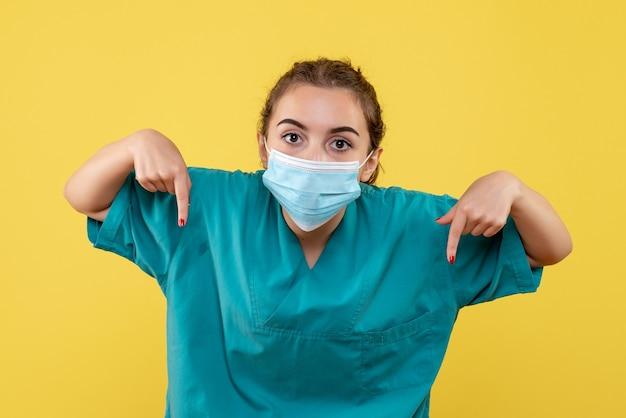 Vooraanzicht vrouwelijke arts in medisch overhemd en masker, uniform virus covid-19 coronavirus pandemie gezondheid