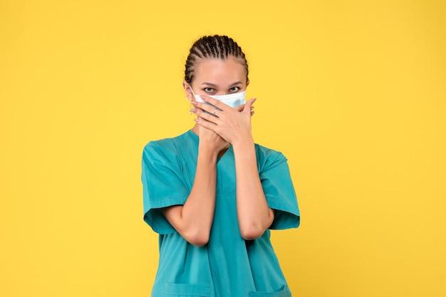 Vooraanzicht vrouwelijke arts in medisch overhemd en masker, verpleegkundige pandemie covid-19 ziekenhuisvirusgezondheid