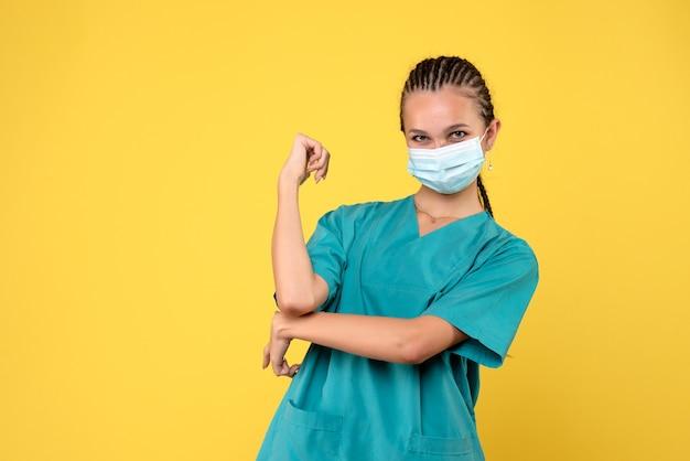 Vooraanzicht vrouwelijke arts in medisch overhemd en masker, verpleegster pandemie ziekenhuis gezondheid covid-