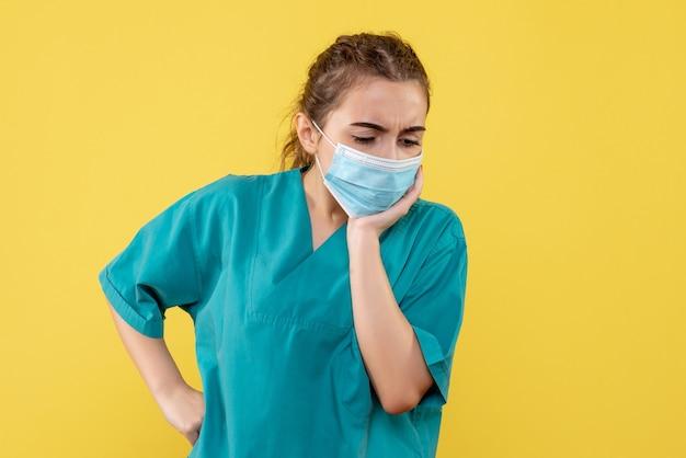 Vooraanzicht vrouwelijke arts in medisch overhemd en masker, virus pandemie covid-19 gezondheid coronavirus