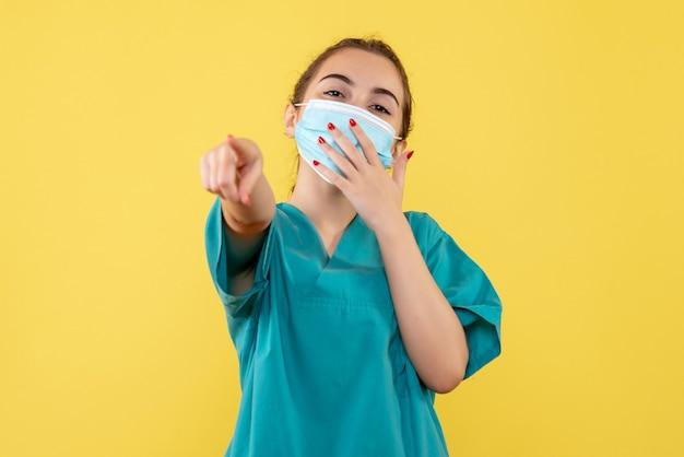 Vooraanzicht vrouwelijke arts in medisch overhemd en masker, virus pandemie uniform covid-19 coronavirus gezondheid