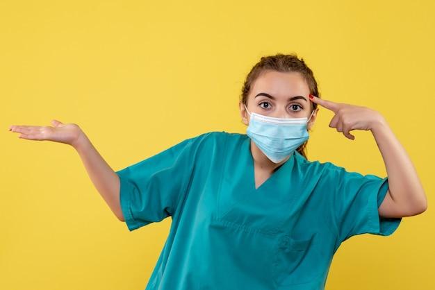 Vooraanzicht vrouwelijke arts in medisch overhemd en masker, virus pandemie uniform gezondheid kleur covid-19 coronavirus