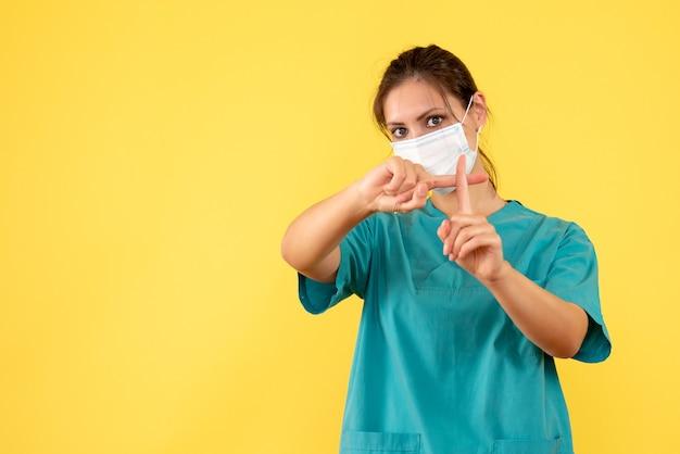 Vooraanzicht vrouwelijke arts in medisch overhemd en met steriel masker op gele achtergrond