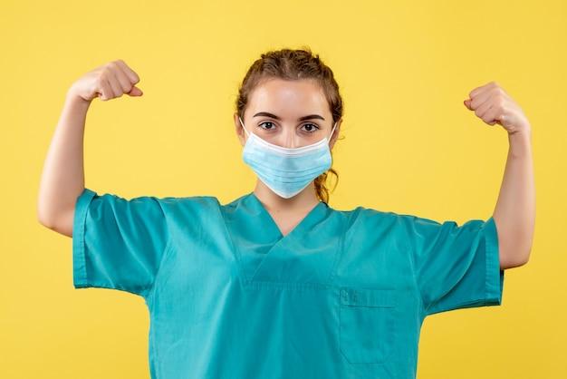 Vooraanzicht vrouwelijke arts in medisch overhemd en steriel masker buigen, gezondheidsvirus uniforme kleur covid-19 emotie