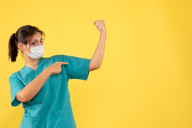 Vooraanzicht vrouwelijke arts in medisch overhemd en steriel masker buigen op gele achtergrond
