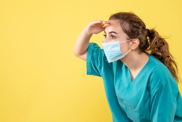 Vooraanzicht vrouwelijke arts in medisch overhemd en steriel masker kijkend naar afstand, gezondheidsvirus uniforme kleur covid-