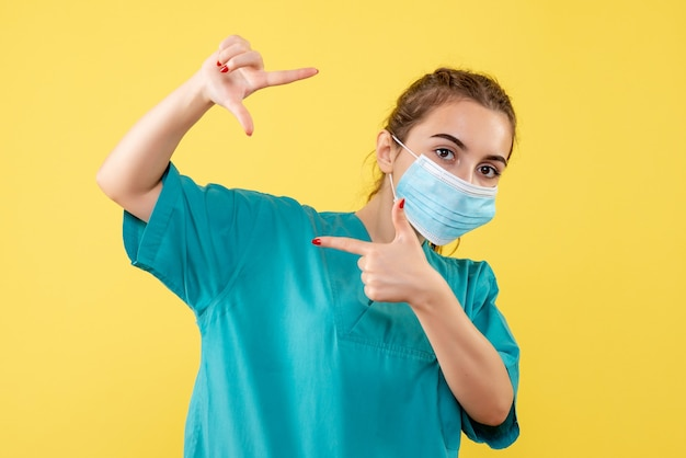Vooraanzicht vrouwelijke arts in medisch overhemd en steriel masker, kleur gezondheid uniform covid-