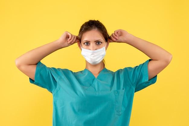 Vooraanzicht vrouwelijke arts in medisch overhemd en steriel masker op gele achtergrond