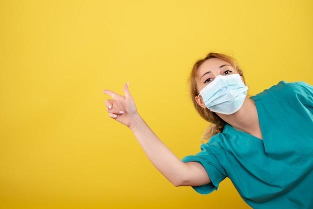 Vooraanzicht vrouwelijke arts in medisch overhemd en steriel masker, ziekenhuiskleur covid-19 pandemie gezondheid emotie