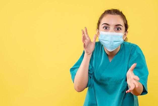 Vooraanzicht vrouwelijke arts in medisch overhemd en steriel masker, ziekte coronavirus virus covid pandemie gezondheid