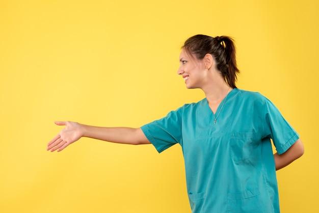 Vooraanzicht vrouwelijke arts in medisch overhemd handen schudden op gele achtergrond