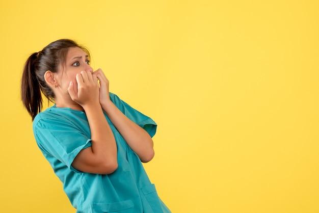 Vooraanzicht vrouwelijke arts in medisch overhemd met bang uitdrukking op gele achtergrond
