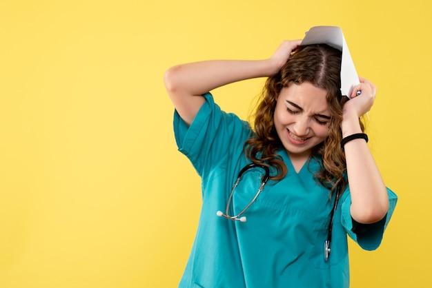 Vooraanzicht vrouwelijke arts in medisch overhemd met papieren analyse met hoofdpijn, uniforme covid-19 gezondheid pandemische virus emotie