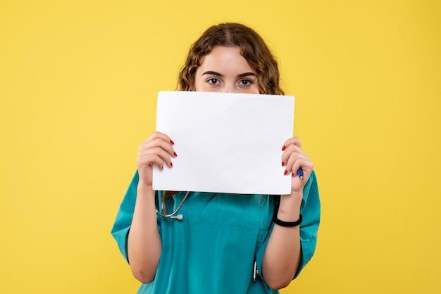 Vooraanzicht vrouwelijke arts in medisch overhemd met papieren analyse, pandemie gezondheid covid-19 uniforme emotie