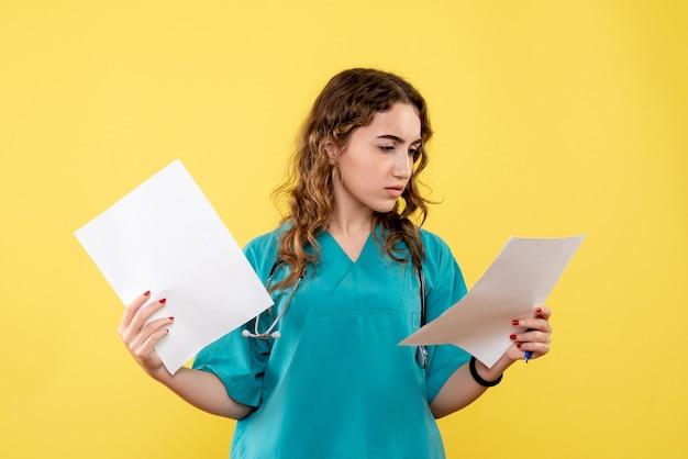 Vooraanzicht vrouwelijke arts in medisch overhemd met papieren analyse, pandemie gezondheidsvirus covid-19 uniforme emotie