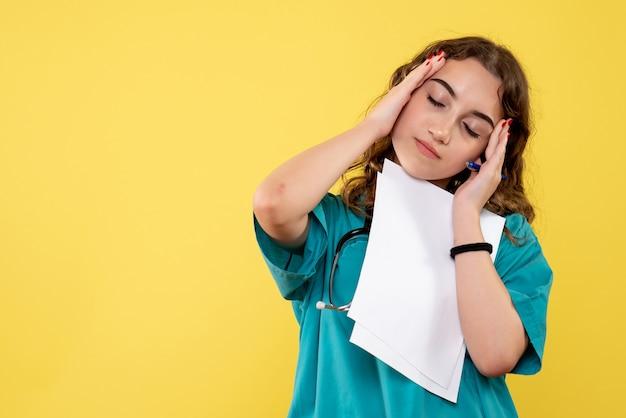 Vooraanzicht vrouwelijke arts in medisch overhemd met papieren analyse, uniform covid-19 gezondheid pandemisch virus emotie