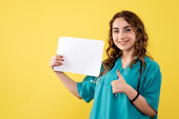 Vooraanzicht vrouwelijke arts in medisch overhemd met papieren analyse, virus pandemie gezondheid covid-19 uniforme emotie