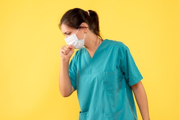 Vooraanzicht vrouwelijke arts in medisch overhemd met steriel masker hoesten op gele achtergrond