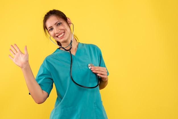 Vooraanzicht vrouwelijke arts in medisch overhemd met stethoscoop op gele achtergrond