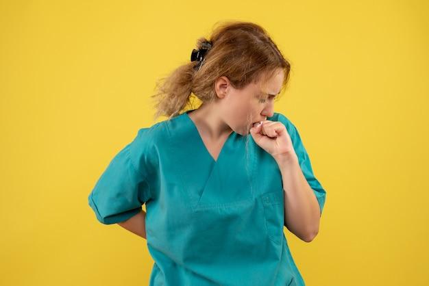 Vooraanzicht vrouwelijke arts in medisch overhemd op geel bureau gezondheidsmedic covid-19 kleur ziekenhuisverpleegkundige