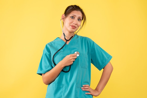 Vooraanzicht vrouwelijke arts in medisch overhemd op gele achtergrond