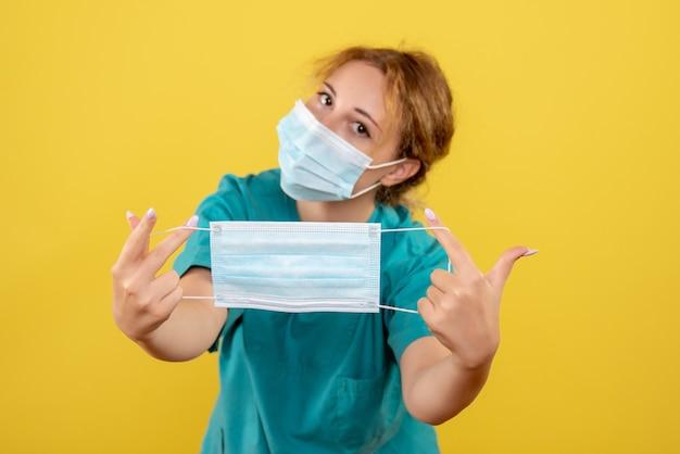 Vooraanzicht vrouwelijke arts in medisch overhemdmasker en met een ander masker, kleur covid-19 virus gezondheid emotie pandemie
