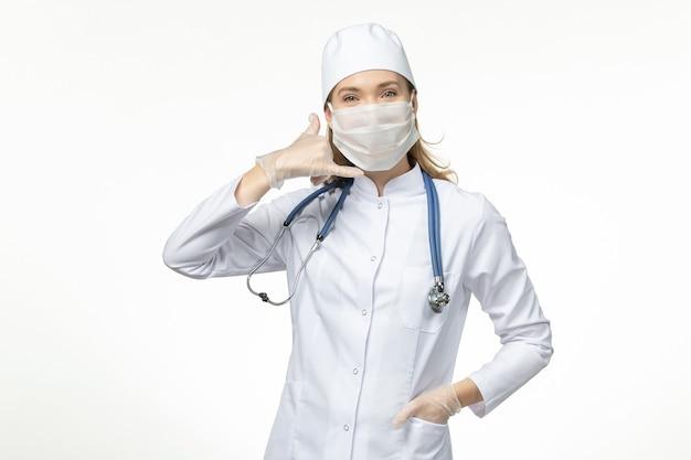 Vooraanzicht vrouwelijke arts in medisch pak draagt ?? masker vanwege coronavirus op lichte witte muur ziekte virus covid- pandemische ziekte ziekte