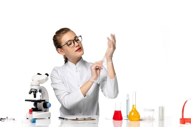 Vooraanzicht vrouwelijke arts in medisch pak handschoenen dragen vanwege covid op een witte ruimte