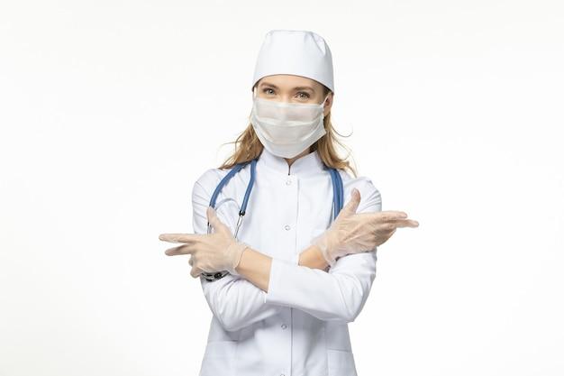 Vooraanzicht vrouwelijke arts in medisch pak masker met handschoenen dragen vanwege coronavirus op witte muur ziekte pandemisch covid-virus