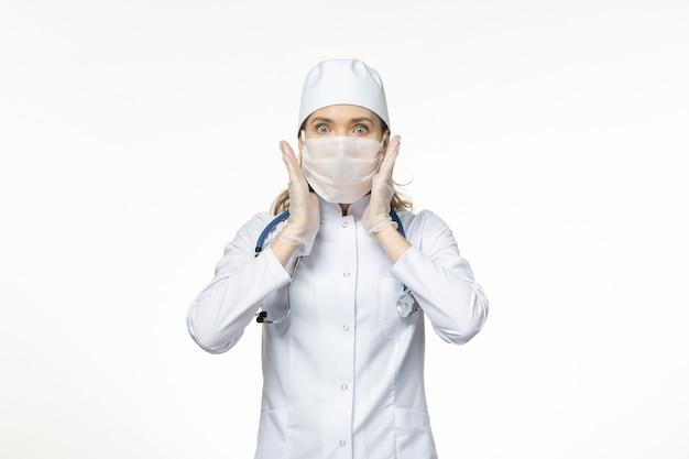 Vooraanzicht vrouwelijke arts in medisch pak met masker vanwege coronavirus op witte muurziekte virus covid- pandemische ziekte ziekte