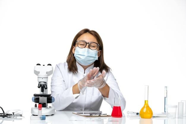 Vooraanzicht vrouwelijke arts in medisch pak met masker vanwege covid lachend op een witte ruimte